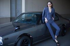 塑造站立在太阳的一辆减速火箭的跑车旁边的女孩 等待在经典汽车附近的一套灰色衣服的时髦的妇女 库存照片