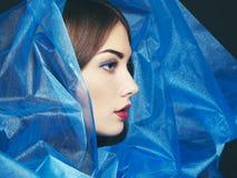 塑造美丽的妇女照片在蓝色面纱下 免版税图库摄影