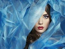 塑造美丽的妇女照片在蓝色面纱之下