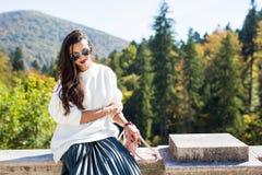 塑造美丽的妇女画象佩带的太阳镜、白色毛线衣和绿色裙子 库存照片