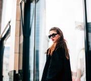 塑造美丽的少妇照片有太阳镜的 式样看的照相机 背景秀丽城市生活方式都市妇女年轻人 女性方式 免版税库存照片