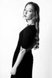 塑造美丽的少妇画象有金发的 一条黑礼服和蓝色项链的女孩在白色背景 染黑  图库摄影