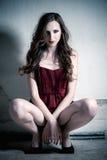 塑造美丽的深色的妇女画象红色礼服的 免版税库存照片