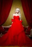 塑造美丽的白肤金发的妇女射击一件长的红色礼服的坐sof 免版税图库摄影