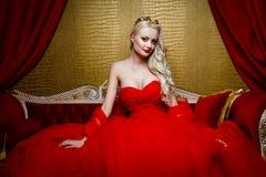 塑造美丽的白肤金发的妇女射击一件长的红色礼服的坐sof 库存图片