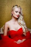 塑造美丽的白肤金发的妇女射击一件长的红色礼服的坐sof 库存照片