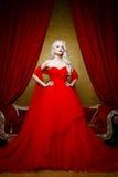 塑造美丽的白肤金发的妇女射击一件长的红色礼服的 库存图片
