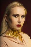 塑造美丽的白肤金发的妇女画象有红色嘴唇和gol的 免版税库存图片