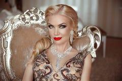 塑造美丽的肉欲的白肤金发的妇女室内画象有ma的 免版税库存照片