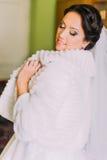 塑造美丽的年轻愉快的新娘画象室内白色皮大衣的 库存照片
