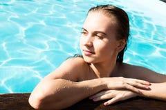塑造美好的摆在被晒黑的游泳池的夏天的比基尼泳装的魅力少妇照片获得乐趣和 免版税库存图片