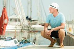 塑造英俊的人画象码头的反对游艇 免版税库存图片