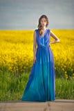 塑造蓝色礼服摆在的美丽的少妇室外与多云剧烈的天空在背景中 可爱的长的头发浅黑肤色的男人 免版税图库摄影
