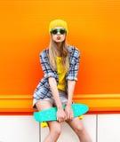 塑造行家太阳镜和五颜六色的衣裳的凉快的女孩 免版税库存照片