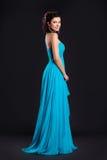 塑造质朴蓝色长礼服微笑的妇女 库存照片