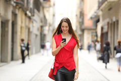 塑造走和使用一个巧妙的电话的妇女 免版税库存照片