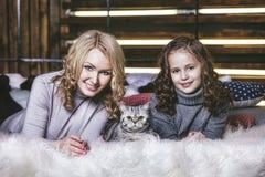塑造逗人喜爱的小女孩和美丽的妇女有英国kitt的 免版税库存照片
