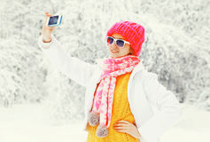 塑造采取在智能手机的冬天妇女图片自画象在穿一条五颜六色的被编织的帽子围巾的多雪的树 免版税库存照片