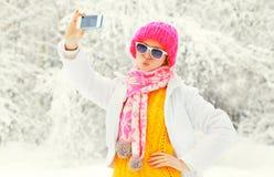 塑造采取在智能手机的冬天妇女照片自画象在穿一条五颜六色的被编织的帽子围巾的多雪的树 免版税库存照片