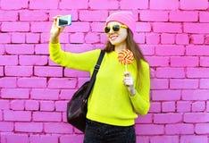 塑造采取照片selfie画象的女孩使用在五颜六色的桃红色的智能手机 库存图片
