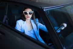 塑造驾驶在一套蓝色衣服的女孩一辆汽车 坐在汽车和拿着方向盘的时髦的妇女 图库摄影