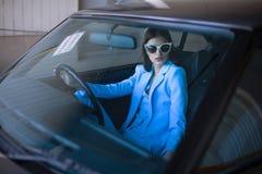 塑造驾驶在一套蓝色衣服的女孩一辆汽车 免版税库存图片
