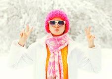 塑造戴五颜六色的被编织的帽子,围巾的冬天少妇获得在多雪的森林公园背景的乐趣 库存照片