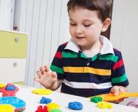 塑造黏土的小男孩 免版税库存照片