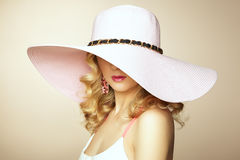 塑造年轻壮观的妇女照片帽子的。女孩摆在 免版税库存图片