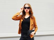 塑造画象俏丽妇女佩带太阳镜、棕色夹克和黑提包在灰色 免版税库存图片