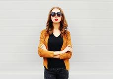 塑造画象有横渡的胳膊佩带的俏丽的妇女太阳镜,在灰色的夹克 免版税库存照片
