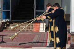 塔什干乌兹别克斯坦- 2011年12月9日:播放karnay的传统长袖衣服的音乐家人 免版税库存照片