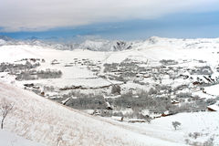 塔吉克斯坦山的村庄在以后的降雪 库存照片