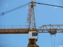 塔吊三角帆和操作员客舱高在明亮的蓝天 库存照片