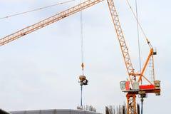 塔吊和工作者倾吐的混凝土在建造场所 库存照片
