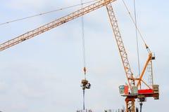 塔吊和工作者倾吐的混凝土在建造场所 图库摄影