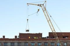 塔吊和未认出的建造者在大厦的建筑 免版税图库摄影