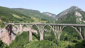 塔拉在塔拉河黑山上的峡谷桥梁Durdevica 由桥梁塔拉峡谷的汽车驱动 强的winde 锁起来 股票视频