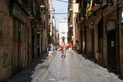 塔拉贡纳,西班牙- 2017年8月28日, :老欧洲镇离开的街道在一个清楚的晴天 明亮的墙壁  库存照片