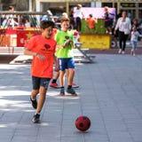 塔拉贡纳,西班牙- 2017年9月17日:有一个足球的男孩在街道上 复制文本的空间 库存图片