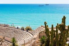 塔拉贡纳,西班牙- 2017年5月1日:古老罗马圆形剧场和海的看法 在前景的仙人掌 复制文本的空间 免版税库存照片