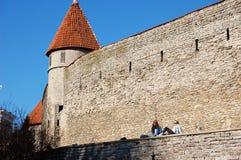 塔林,爱沙尼亚, 05/02/2017女孩坐加州的墙壁 库存照片