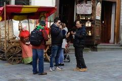 塔林,爱沙尼亚- 2017年4月11日:游人在耶路撒冷旧城 杏仁坚果的卖主在全国中世纪礼服的 免版税库存照片