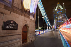 塔桥梁在伦敦在与汽车左航行灯的晚上 免版税图库摄影