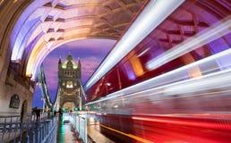 塔桥梁在有通过被弄脏的红色的公共汽车的伦敦  免版税图库摄影