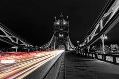 塔桥梁在黑白的伦敦,英国在与迷离的晚上上色了汽车光 库存照片