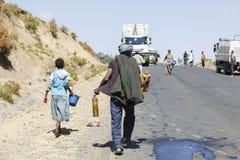 塔的斯亚贝巴,埃塞俄比亚,2015年1月15日:本机用溢出在一辆被弄翻的罐车外面的柴油填满他们的罐 免版税库存照片