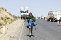 塔的斯亚贝巴,埃塞俄比亚,2015年1月15日:本机用溢出在一辆被弄翻的罐车外面的柴油填满他们的罐 免版税库存图片