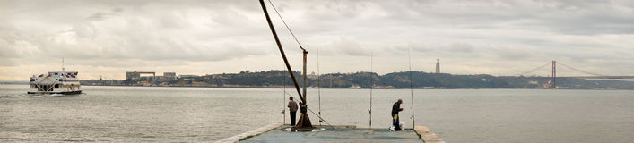 塔霍河的全景在有渡轮、渔夫,克里斯多Rei雕象和25的de Abril Bridge里斯本 免版税库存图片