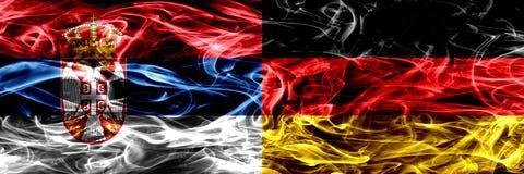 塞尔维亚对德国,肩并肩被安置的德国烟旗子 浓厚 免版税库存照片